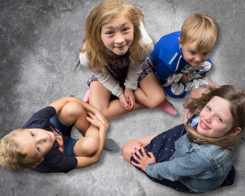 Vier kleinkinderen zittend in een cirkel.